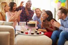 Grupp av vänner som hemma firar födelsedag tillsammans arkivfoto