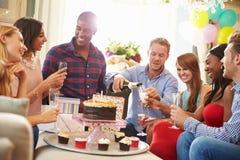 Grupp av vänner som hemma firar födelsedag tillsammans royaltyfri bild