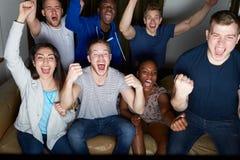 Grupp av vänner som hemma håller ögonen på television tillsammans Arkivfoto