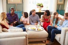 Grupp av vänner som hemma kopplar av med drinkar tillsammans royaltyfri foto