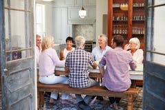 Grupp av vänner som hemma tycker om mål tillsammans arkivbilder