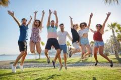 Grupp av vänner som hoppar som lyfter tillsammans händer Royaltyfria Foton