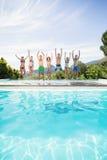 Grupp av vänner som hoppar på poolsiden Arkivfoto