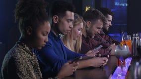 Grupp av vänner som knyter kontakt på telefoner i nattklubb lager videofilmer