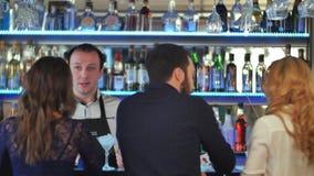 Grupp av vänner som kopplar av på partiet i stång som talar med bartendern Royaltyfri Foto