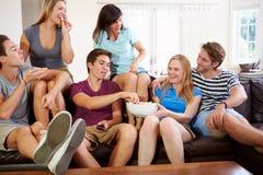 Grupp av vänner som kopplar av på Sofa At Home Together Fotografering för Bildbyråer