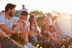 Grupp av vänner som kopplar av utvändiga tält på campa ferie royaltyfri fotografi