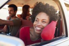 Grupp av vänner som kopplar av i bil under vägtur arkivfoton
