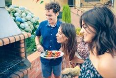 Grupp av vänner som lagar mat i en sommargrillfest Arkivfoto