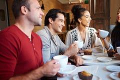 Grupp av vänner som möter i kaférestaurang Arkivfoto