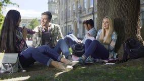Grupp av vänner som påverkar varandra mellan de sammanträde under träd, förhållande arkivfilmer