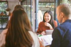 Grupp av vänner som pratar och använder bärbara datorn i kafé på coffee shopkafét i universitet som tillsammans talar och skratta arkivfoton