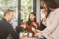 Grupp av vänner som pratar och använder bärbara datorn i kafé på coffee shopkafét i universitet som tillsammans talar och skratta arkivbilder