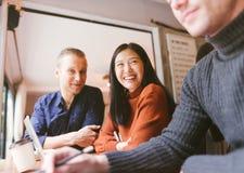 Grupp av vänner som pratar och använder bärbara datorn i kafé på coffee shopkafét i universitet som tillsammans talar och skratta arkivbild