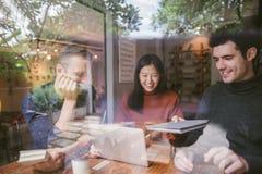 Grupp av vänner som pratar och använder bärbara datorn i kafé på coffee shopkafét i universitet som tillsammans talar och skratta fotografering för bildbyråer