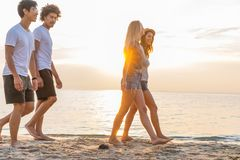 Grupp av vänner som promenerar en strand på sommartid Lyckliga ungdomarsom tycker om en dag på stranden arkivbilder