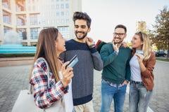 Grupp av vänner som promenerar gatan med shoppingpåsar royaltyfria bilder