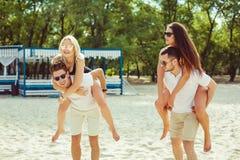 Grupp av vänner som promenerar stranden, med män som på ryggen ger ritt till flickvänner Arkivbild