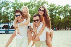 Grupp av vänner som promenerar stranden, med män som på ryggen ger ritt till flickvänner Royaltyfri Bild