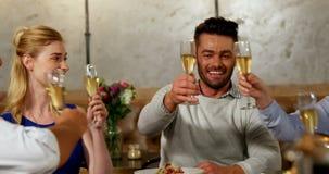 Grupp av vänner som rostar champagneexponeringsglas på matställetabellen 4K 4k arkivfilmer
