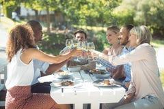 Grupp av vänner som rostar exponeringsglas av vin i en restaurang Arkivfoto