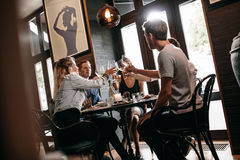 Grupp av vänner som rostar på restaurangen Arkivfoton