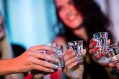 Grupp av vänner som rostar tequilaskottexponeringsglas fotografering för bildbyråer
