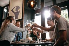 Grupp av vänner som rostar vin på kafét Arkivbild