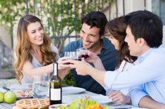 Grupp av vänner som rostar vinexponeringsglas Arkivbilder