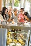 Grupp av vänner som ser cakescafen Arkivbild
