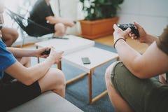 Grupp av vänner som sitter på en soffa i vardagsrum och spelar videospel Begrepp för avslappnande tid för familj hemmastatt Royaltyfria Bilder