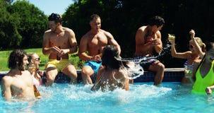 Grupp av vänner som sitter på pölsidan och tycker om drinkar lager videofilmer
