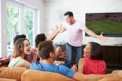 Grupp av vänner som sitter på Sofa Watching Soccer Together Arkivfoto