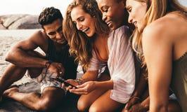 Grupp av vänner som sitter på stranden som har gyckel royaltyfri fotografi