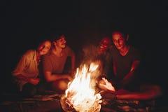 Grupp av vänner som sitter runt om en brasa på en campingplats royaltyfri bild