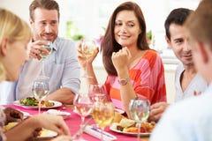 Grupp av vänner som sitter runt om tabellen som har matställepartiet Royaltyfri Foto