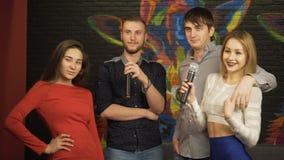 Grupp av vänner som sjunger karaoke i en nattklubb långsam rörelse arkivfilmer