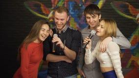 Grupp av vänner som sjunger karaoke i en nattklubb långsam rörelse lager videofilmer