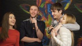 Grupp av vänner som sjunger karaoke i en nattklubb långsam rörelse stock video