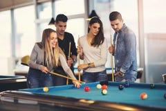 Grupp av vänner som spelar billiard Royaltyfria Bilder