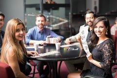 Grupp av vänner som spelar bingo royaltyfri foto