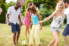 Grupp av vänner som spelar fotboll i trädgård Arkivfoto