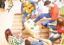 Grupp av v?nner som spelar gitarren och hemma dricker ungdomarf?r ?l och f?r whisky - lyckligt m?te i vardagsrummet arkivfoto