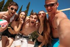 Grupp av vänner som spelar strandsalvan - Mång--etik grupp människor som har gyckel på stranden royaltyfri fotografi