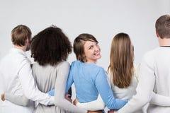 Grupp av vänner som står armen i arm Royaltyfri Foto