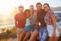 Grupp av vänner som står med bilen på den kust- vägen på solnedgången arkivfoton
