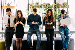 Grupp av vänner som står på tabellen och bläddrar i deras divices i modernt rum royaltyfri foto