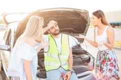 Grupp av vänner som strandas på parkeringsplatsen av en bruten bil under vägtur royaltyfria foton