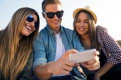 Grupp av vänner som tar en selfie med smartphonen Royaltyfri Foto