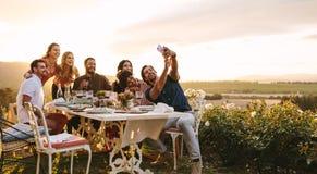 Grupp av vänner som tar selfie på matställepartiet fotografering för bildbyråer